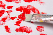Close up of paint brush with red paint strokes over white — Stock Photo