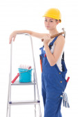 Young beautiful woman in blue coveralls with builder's tools and — Stock Photo