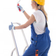 Young woman painter in blue builder uniform standing on ladder w — Stock Photo #61843847