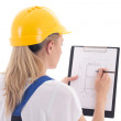 Back view of woman in blue builder uniform holding building sche — Stock Photo #61843887
