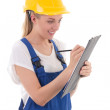 Young woman in blue builder uniform writing something on clipboa — Stock Photo #61843891
