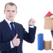 Moving day concept - business man with metal key and girl with b — Stock Photo #63373869