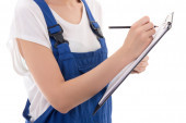 Clipboard and pen in woman builder hands isolated on white — Stock Photo
