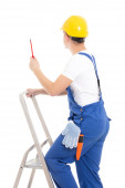 Back view of young man builder in blue coveralls with screwdrive — Stock Photo