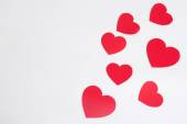 Red paper hearts over white with copy space — Stock fotografie