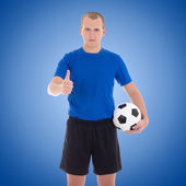 Soccer player with a ball thumbs up over blue — Stock Photo