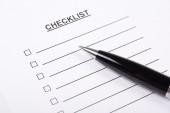 Chiuda in su della penna ed elenco di controllo in bianco — Foto Stock