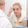 Beautiful woman with problem skin looking at mirror in bathroom — Stock Photo #67968897