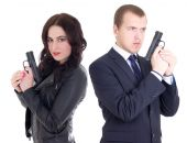 Young man in business suit and elegant woman with guns isolated  — Foto de Stock