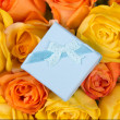 Little blue gift box and beautiful bouquet of roses — Stock Photo #68548539