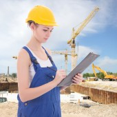 Attractive woman builder writing something in clipboard — Stok fotoğraf