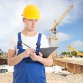 Jeune bel homme en uniforme avec presse-papiers à constru builder — Photo
