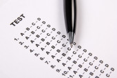 Close up of test score sheet with answers and pen — Stock Photo