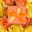 Little gift box and beautiful bouquet of roses — Stock Photo #69696953