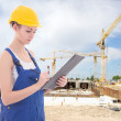 Young attractive woman builder writing something in clipboard — Stock Photo #69891435