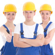 Two young women and man in blue builder 's uniform isolated on w — Stock Photo #69891603
