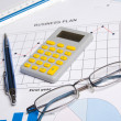 Business papers with graphs, charts, glasses, pen and calculator — Stock Photo #70277373