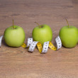Three green apples and measure tape on table — Stock Photo #70278053