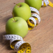 Close up of three green apples and measure tape on table — Stock Photo #70278243