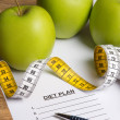 Diet concept - paper with diet plan, apples and measure tape on — Stok fotoğraf #71651121