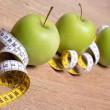 Diet concept - close up of green apples and measure tape on tabl — Stock Photo #71651269