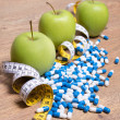 Diet concept - green apples, pills and measure tape on table — Stock Photo #71651317