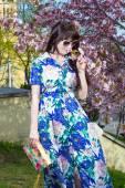 Beautiful woman posing over blooming sakura tree in park — Stock Photo