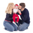 Happy young family - father and mother kissing little daughter i — Stock Photo #73555955