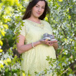 Beautiful pregnant woman holding little shoes in blooming cherry — Stock Photo #73837551