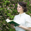 Dreamy beautiful woman reading book in blooming spring garden — Stock Photo #74084347