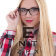 Portrait of blondie woman in eyeglasses with eye test chart — Stock Photo #74351033