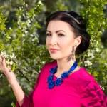 Young beautiful woman in cherry-tree garden — Stock Photo #74471545
