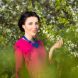 Portrait of young beautiful woman in garden with blooming trees — Stock Photo #74471569