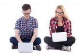 Teenage girl and boy sitting with laptops isolated on white — Stock Photo