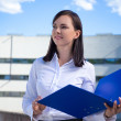 Beautiful business woman holding blue folder — Stock Photo #76582143