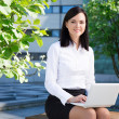 Business woman using laptop in city park — Stock Photo #76582267