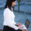 Business woman using laptop in city park — Stock Photo #76582397