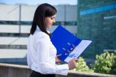 Beautiful business woman holding folder with business plan  — Stok fotoğraf
