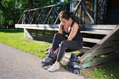 Young woman sitting and putting on skates in park — Stock Photo