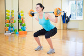Beautiful sporty woman exercising with barbell in gym — Stock Photo