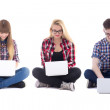 Two teenage girls and one boy sitting with laptops isolated on w — Stock Photo #78209462