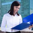Beautiful business woman holding folder with documents — Stock Photo #78392364
