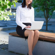Young business woman using laptop in city park — Stock Photo #78392494