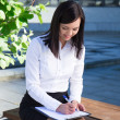 Young business woman writing something on clipboard in city park — Stock Photo #78392530