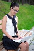 Attraente ragazza in uniforme scolastica utilizzando il computer portatile nel parco o campus — Foto Stock