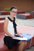 Portrait of teenage girl sitting on bench and reading something — Stock Photo