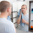 Hygiene concept - handsome man looking at mirror after shaving i — Stock Photo #78786206
