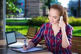 Heureux étudiant ou écolière parler téléphone mobile dans le parc — Photo