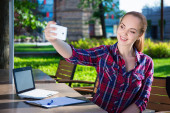 Teenage girl making selfie photo with smart phone in park — Stock Photo