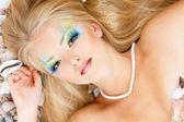 Girl mermaid with  make-up lying on beach — Stock Photo